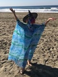 Redwing Keyssar standing on a beach wearing a witch hat, arms spread wide in the air.