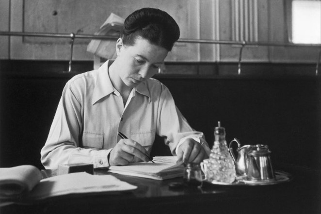Beauvoir at café Deux Magots in 1944. She is sitting at a table writing in a notebook.