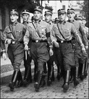 Young Nazi soldiers marching down a street in Germany.