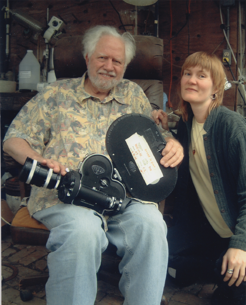 Sasha Shulgin sitting with  movie camera on his lap with Connie Littlefield beside him.