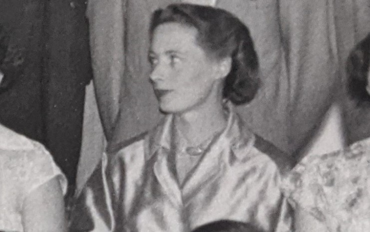 Jane Osmond, a white woman in her 30s, looks to the left while wearing a gold coat