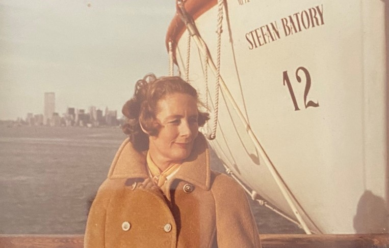 """Jane Osmond, a middle-aged white woman, stands in front of a ship called the """"Stefan Batory"""" in the New York City Harbour. Jane is wearing an orange-tan peacoat and is gazing to the right."""