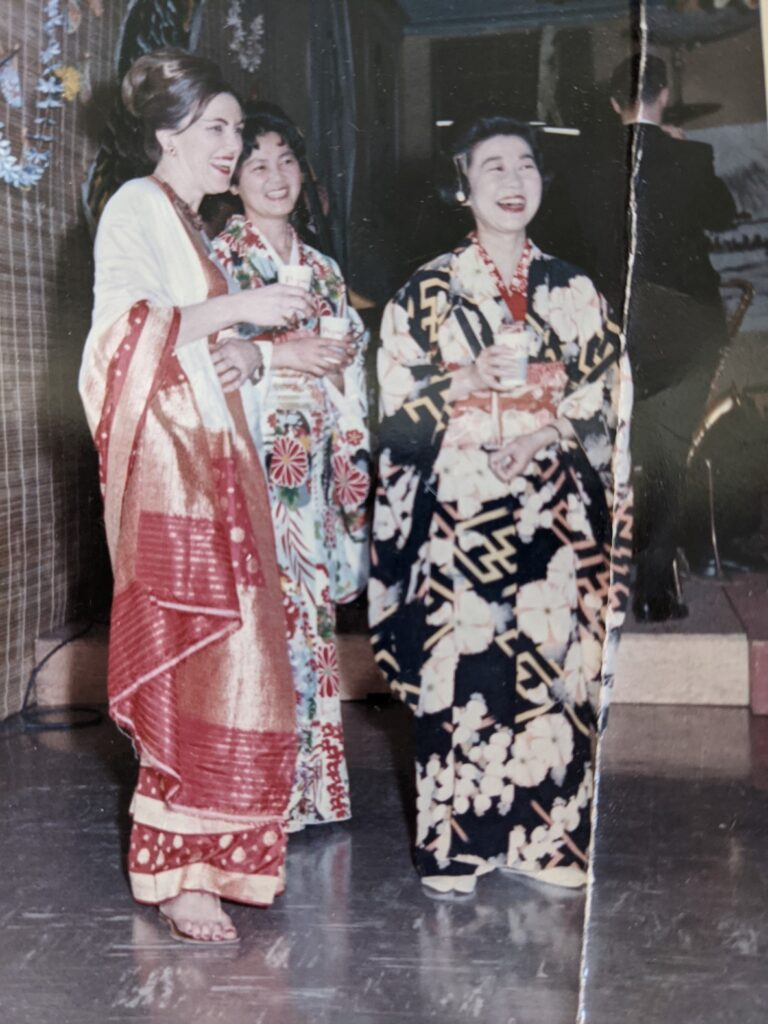 Three women (one white and two Japanese) stand smiling dressed in traditional Japanese garb