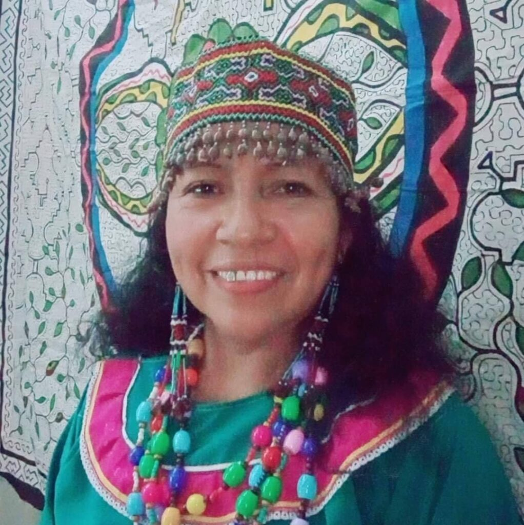Wilma Mahua Campos in traditional Inkan garb standing in front of her artwork.